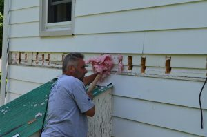 man placing insulating into exterior wall
