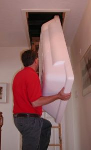 man putting white cover into attic