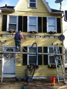 man inputting insulation in yellow house